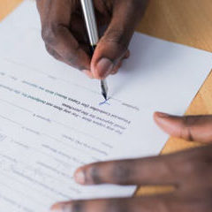 The hand signing a contract on paper